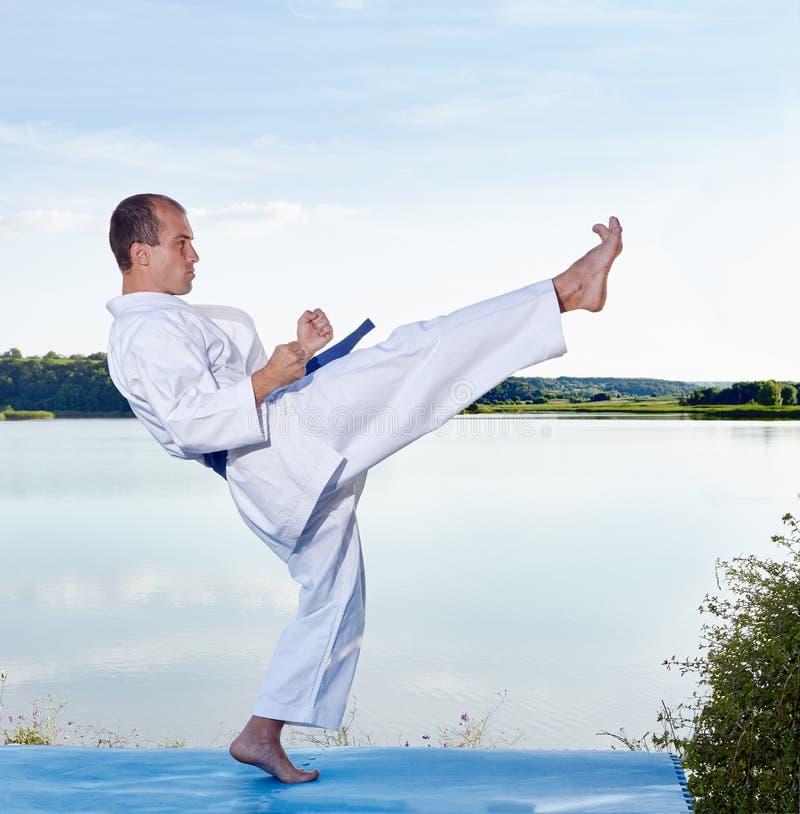 L'atleta adulto colpisce una gamba di scossa sul lago fotografia stock libera da diritti