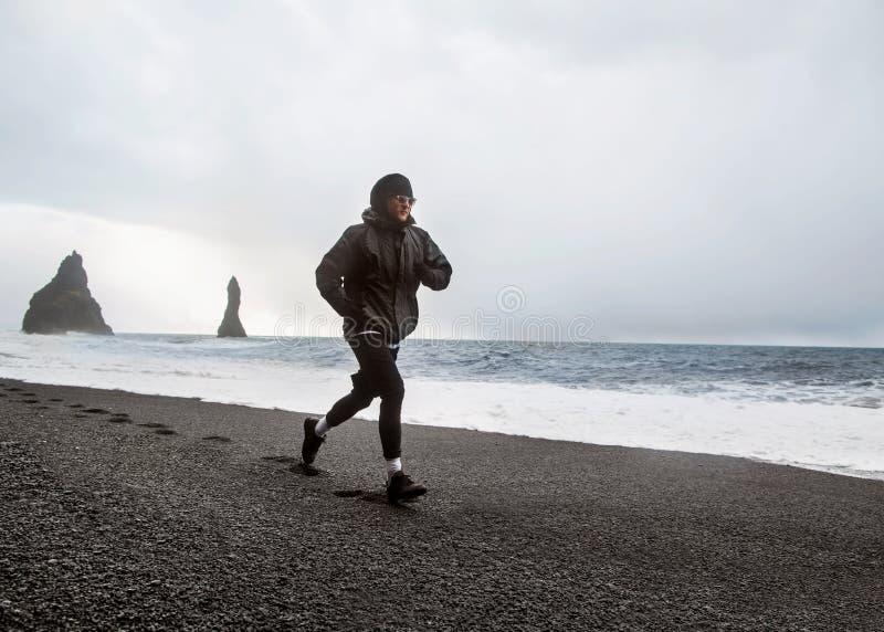 L'atleta del tipo funziona su una spiaggia nera in Islanda fotografia stock libera da diritti