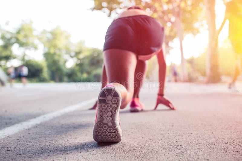 L'atleta della donna nell'insieme pronto va posizione da cominciare correre fotografia stock libera da diritti