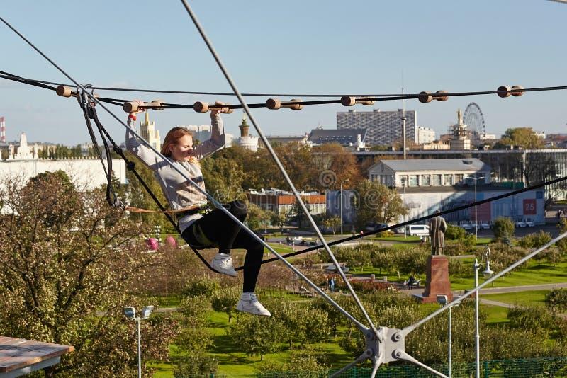 L'atleta della ragazza esegue una corsa ad ostacoli in parco rampicante fotografia stock libera da diritti