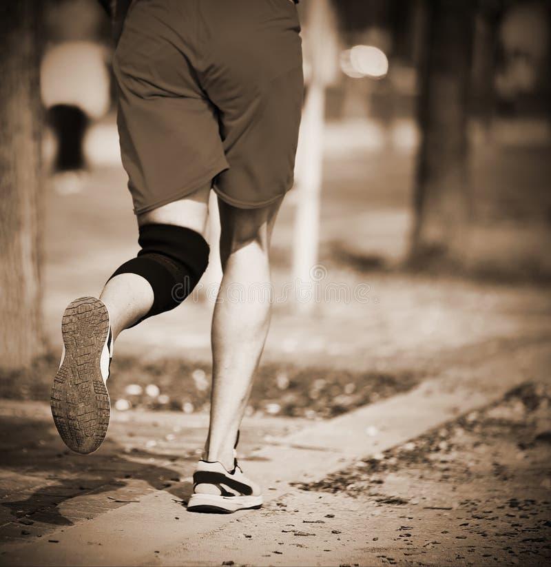 L'atleta esegue la corsa con la fasciatura del ginocchio immagine stock