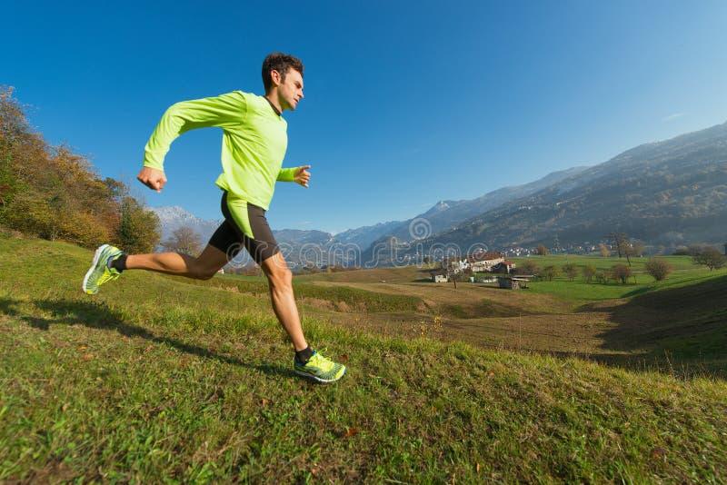 L'atleta funziona in discesa nel prato in una valle dell'italiano A immagini stock