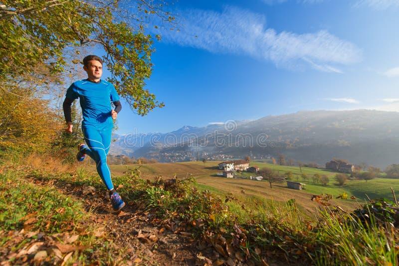 L'atleta funziona sulla traccia di montagna in una valle delle alpi italiane immagine stock libera da diritti