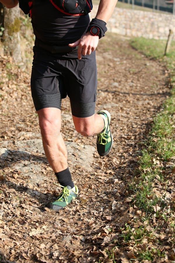 L'atleta funziona velocemente durante la corsa di triathlon sulla montagna immagini stock libere da diritti