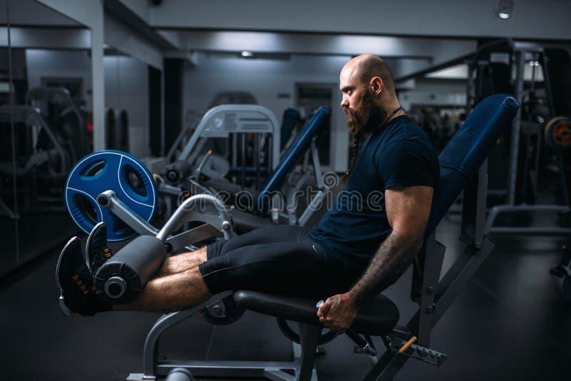 L'atleta muscolare prepara le gambe sulla macchina di esercizio fotografie stock