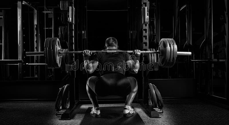 L'atleta professionista si siede con un bilanciere sulle suoi spalle e PR fotografia stock