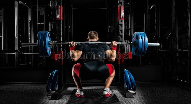 L'atleta professionista si siede con un bilanciere sulle suoi spalle e PR fotografia stock libera da diritti