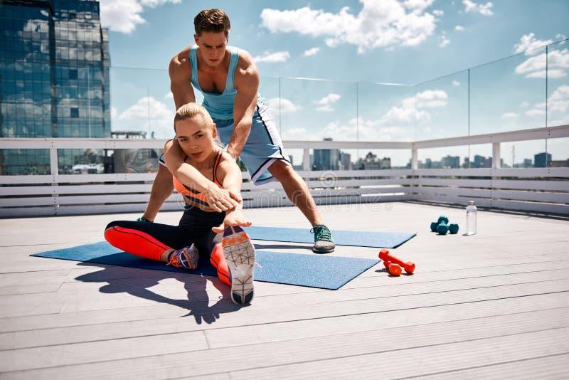 L'atleta sta aiutando l'amica con l'allungamento fuori fotografia stock