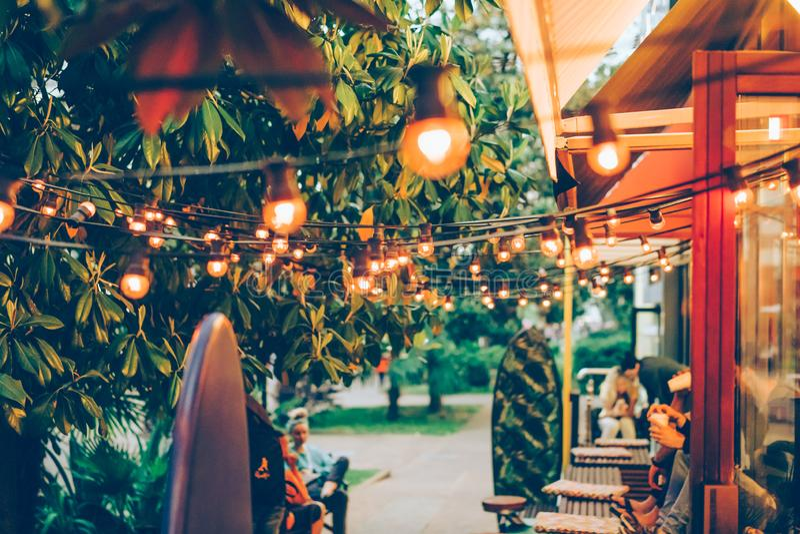 L'atmosphère amicale de la jeunesse dans une terrasse extérieure confortable d'été dans un café photo stock