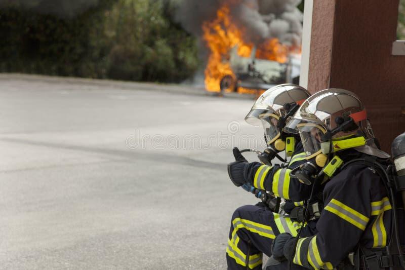 L'attac binomial de sapeur-pompier français sur le feu de voiture indiquent correct image stock