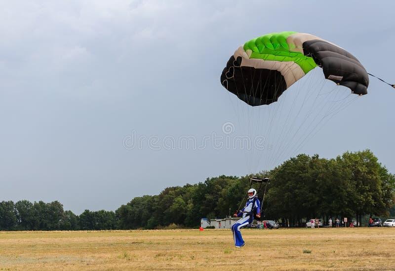 L'atterrissage coloré de parachute comme tempête vient images stock