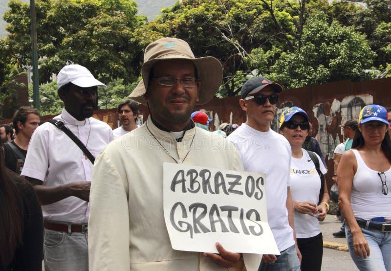 L'attivista religioso distribuisce gli abbracci liberi a Caracas Venezuela in mezzo delle proteste violente a Caracas contro il g fotografia stock libera da diritti