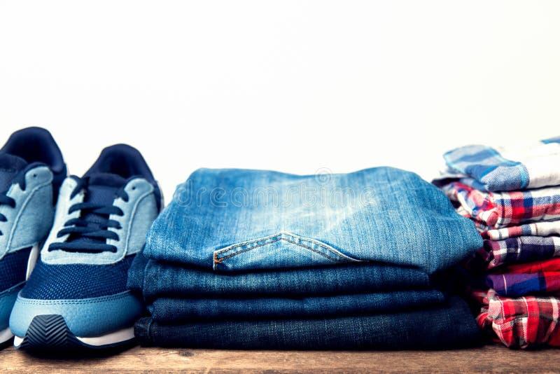 L'attrezzatura casuale degli uomini freschi di modo sulla tavola di legno, d'avanguardia di estate, maglietta, pantaloni delle bl immagine stock