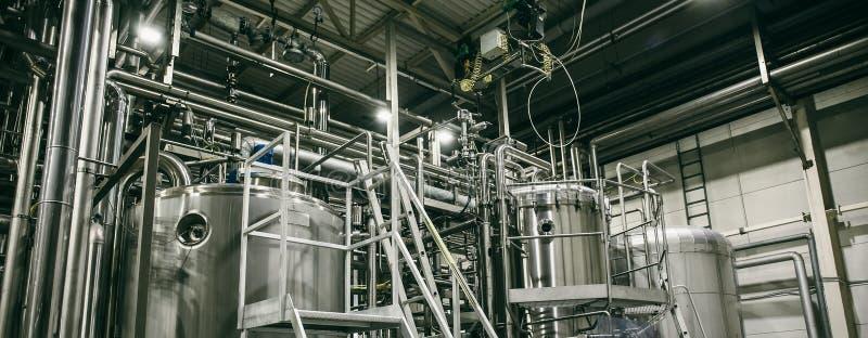 L'attrezzatura della fabbrica di birra, tubi industriali dell'acciaio inossidabile si è collegata con i carri armati o i tini per fotografia stock