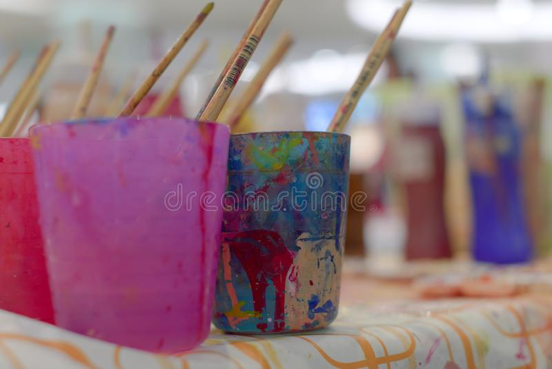 L'attrezzatura variopinta dell'acquerello quale il vetro dei paintbrushs ed il vassoio di colore sono disponibili per i bambini immagine stock