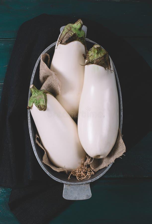 L'aubergine blanche sur des textiles avec l'herbe sèche dans une cuvette ronde sur la moquerie en bois, fond noir de l'espace de  photo stock