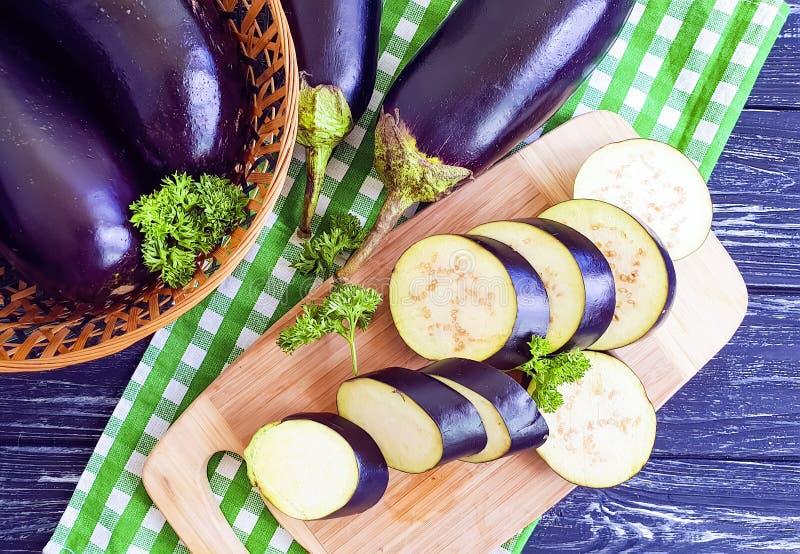 L'aubergine a découpé le cuisinier en tranches d'ingrédient de préparation de ‹d'†de ‹d'†sur le fond en bois de fond en bois images stock