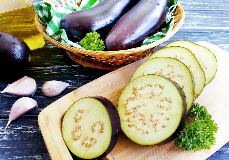 L'aubergine a découpé le cuisinier en tranches de vert d'ingrédient de préparation de ‹d'†de ‹d'†sur le fond en bois de fond  image stock