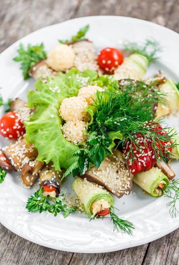 L'aubergine grillée roule et la courgette roule avec des tomates, des champignons, des herbes, des boules de fromage et le sésame photographie stock libre de droits