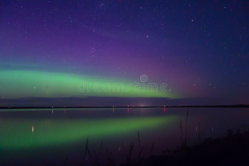 L'aurora borealis del magenta e di verde blu ha riflesso sopra un lago fotografia stock