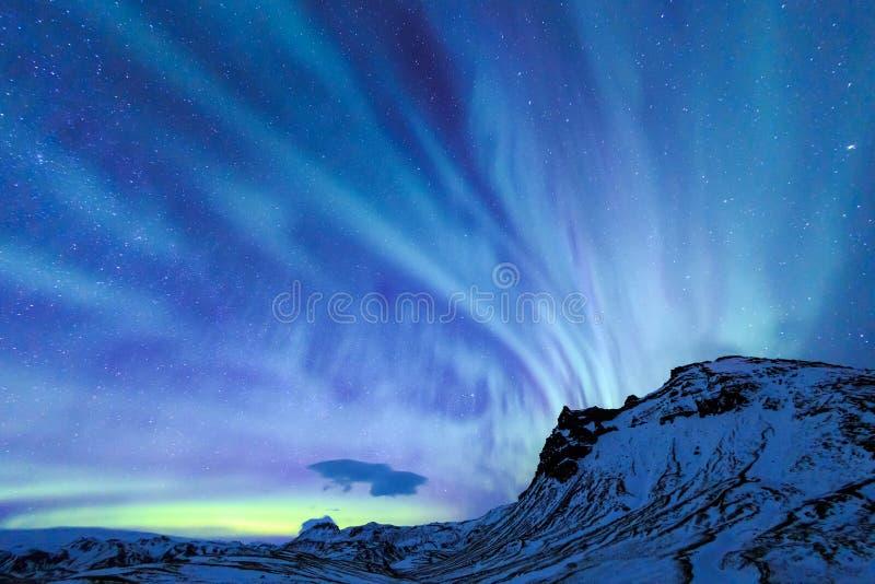 L'aurora della luce nordica più alla montagna della neve fotografie stock
