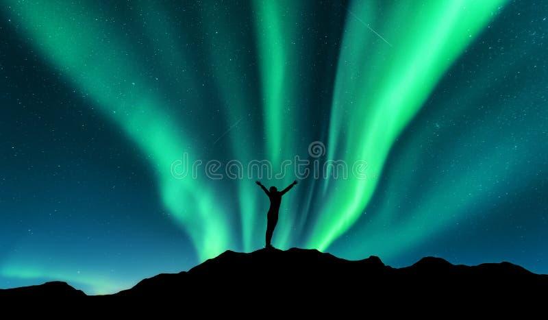 L'aurore et silhouette de femme debout avec augmentés les bras sur la montagne en Norvège Aurora Borealis photo stock