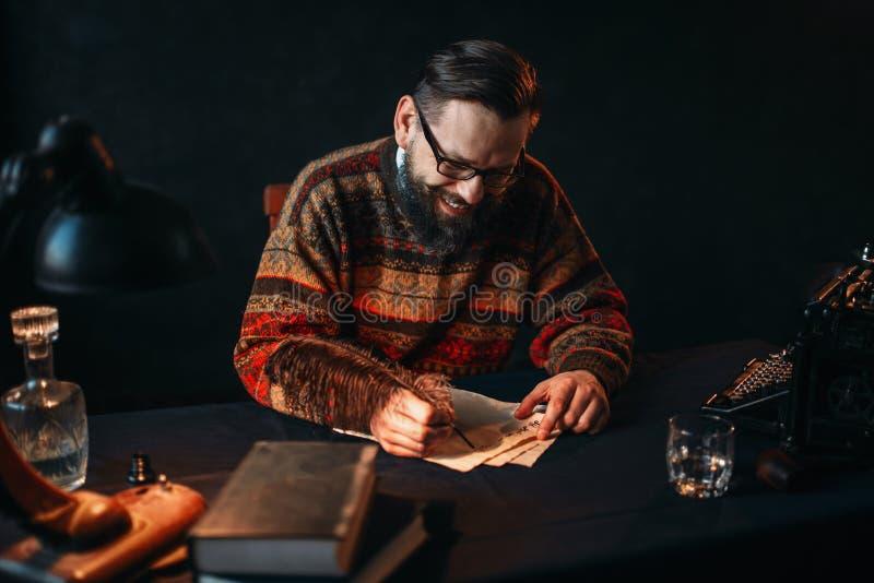 L'auteur barbu en verres écrit avec une plume photo libre de droits