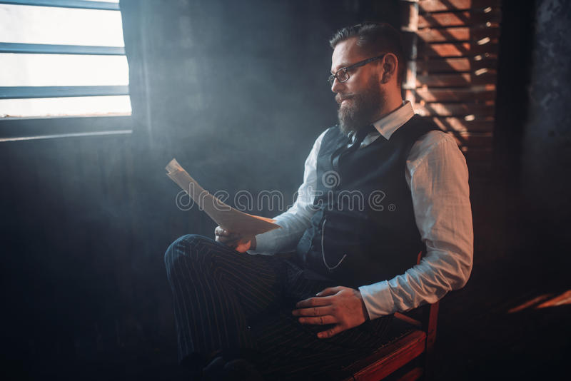 L'auteur barbu en verres lit le texte manuscrit images libres de droits