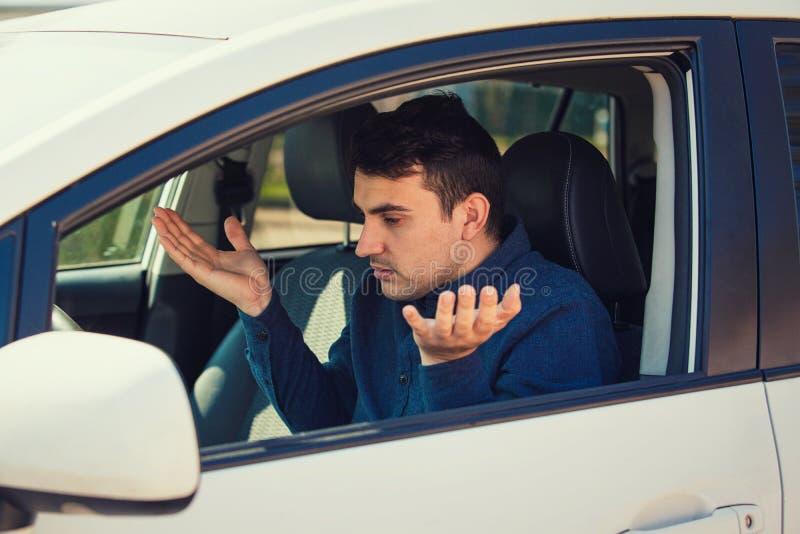 L'autista arrabbiato del giovane, ha scocciato stringendo le mani e scrollando le spalle le spalle, ha problemi con l'automobile immagini stock