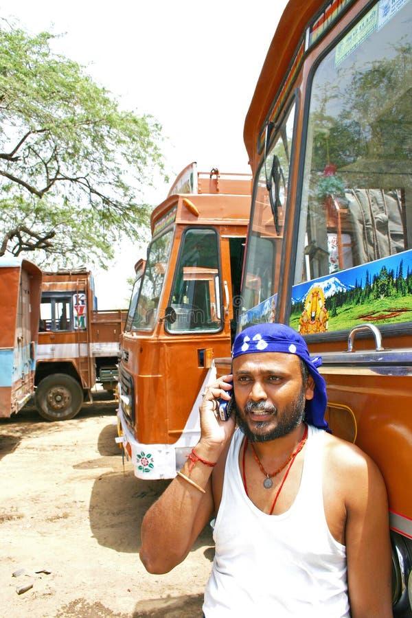 L'autista di camion indiano che parla sul suo telefono cellulare con i camion ha parcheggiato sul suo indietro immagine stock libera da diritti