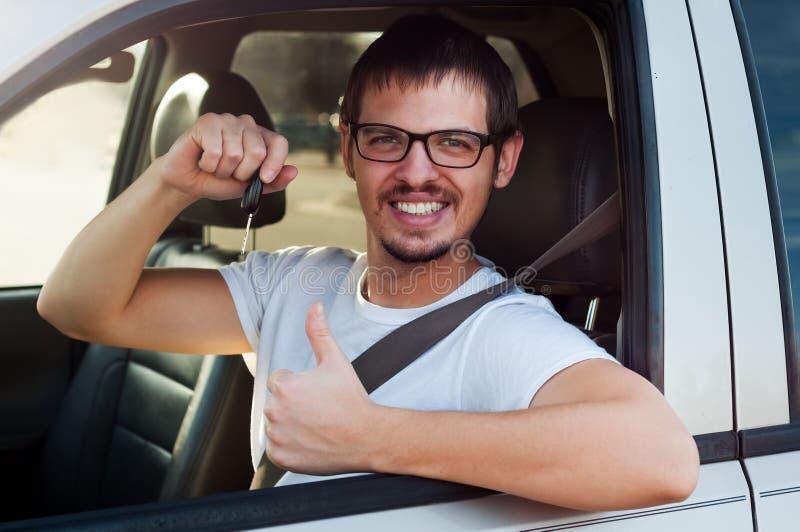 L'autista sorridente sta tenendo le chiavi dell'automobile fotografia stock
