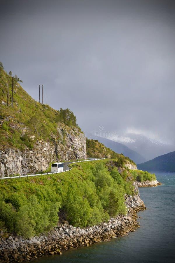 L'autobus blanc conduit le long d'une route sur un flanc de coteau vert avec la mer vers le bas ci-dessous photos libres de droits