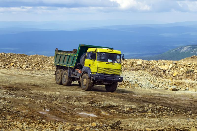 L'autocarro con cassone ribaltabile sta guidando su una strada della montagna fotografia stock