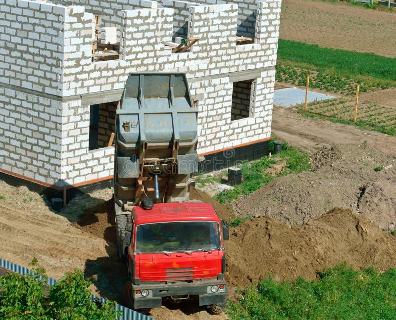 L'autocarro con cassone ribaltabile vicino alla casa in costruzione, il camion e la costruzione della casa da un mattone bianco,  fotografia stock libera da diritti