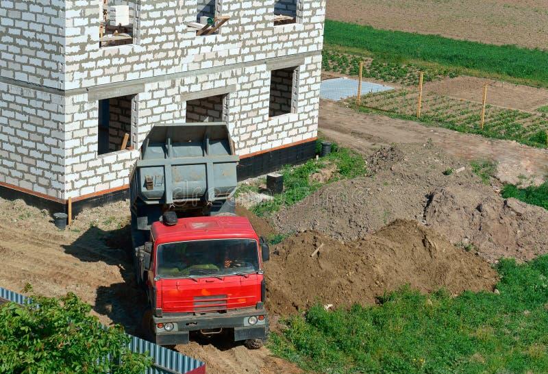 L'autocarro con cassone ribaltabile vicino alla casa in costruzione, il camion e la costruzione della casa da un mattone bianco,  immagini stock libere da diritti