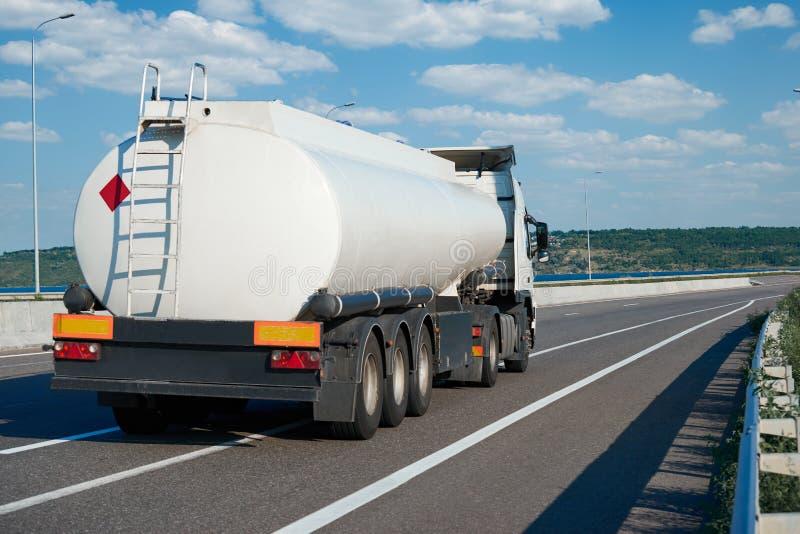 L'autocisterna guida sulla strada principale, cisterna in bianco bianca per olio, retrovisione, un oggetto sulla strada immagini stock libere da diritti
