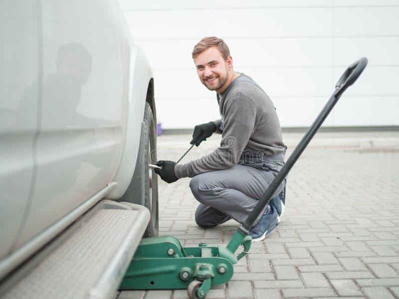 L'automatique-travailleur change la roue de la machine et du sourire outside photos stock