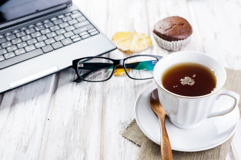 L'automne encore la vie avec tasse de thé, ordinateur portable, lunettes et feuilles photographie stock