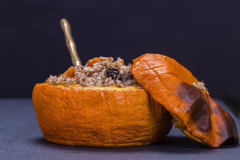 L'automne fait maison a bourré le potiron avec du sarrasin, la carotte, l'oignon, l'ail et les pruneaux sur le fond de l'ardoise  photos libres de droits
