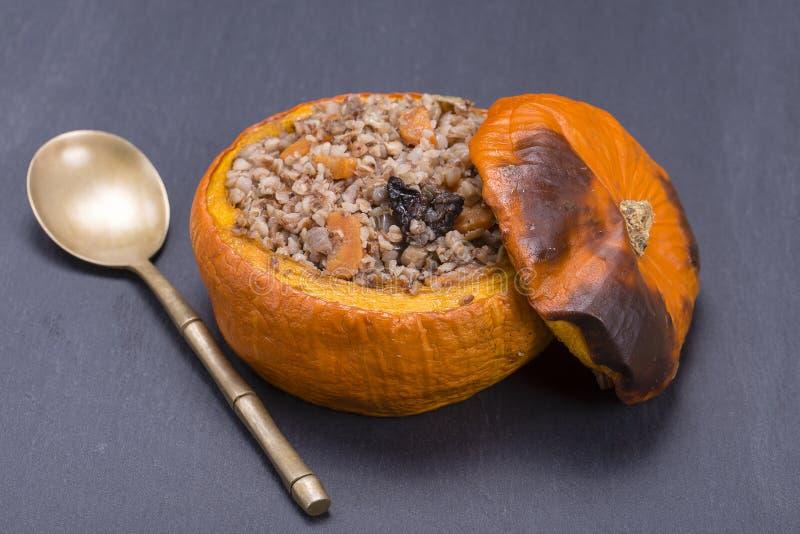 L'automne savoureux a bourré le potiron avec du sarrasin, la carotte, l'oignon, l'ail et les pruneaux sur le fond de l'ardoise no photos stock