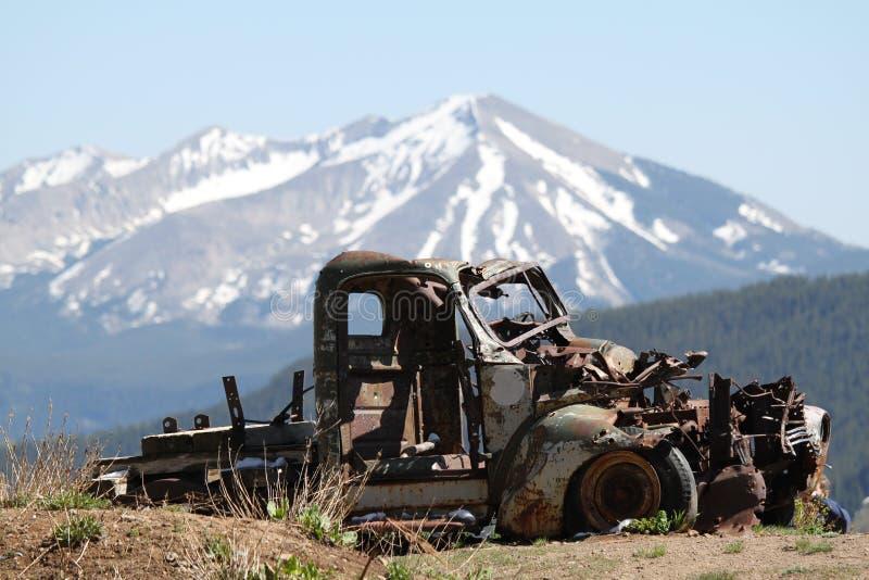 L'automobile arrugginita rimane in montagne rocciose immagini stock libere da diritti