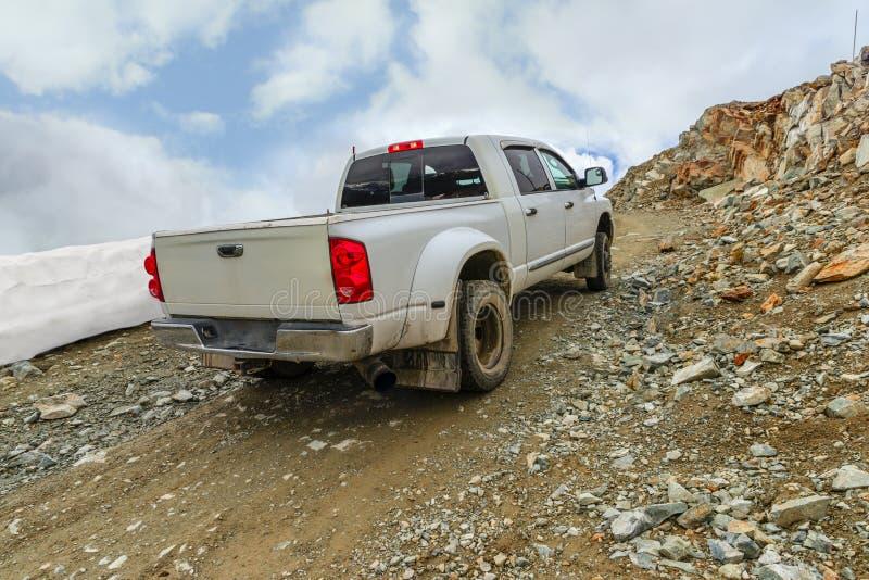 L'automobile bianca con un corpo guida su una strada pietrosa alla cima di una roccia fotografie stock libere da diritti