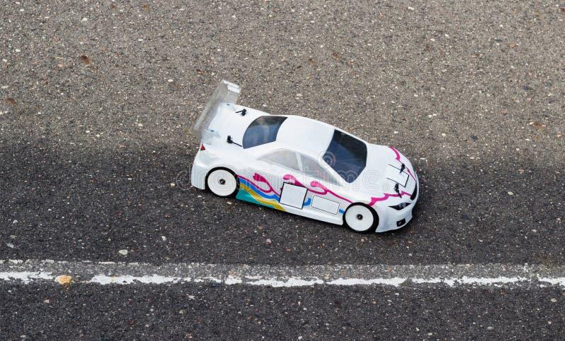 L'automobile bianca radio-controllata su una pista dell'asfalto, il primo piano, concorsi in automobile radio-controllata mette i immagine stock