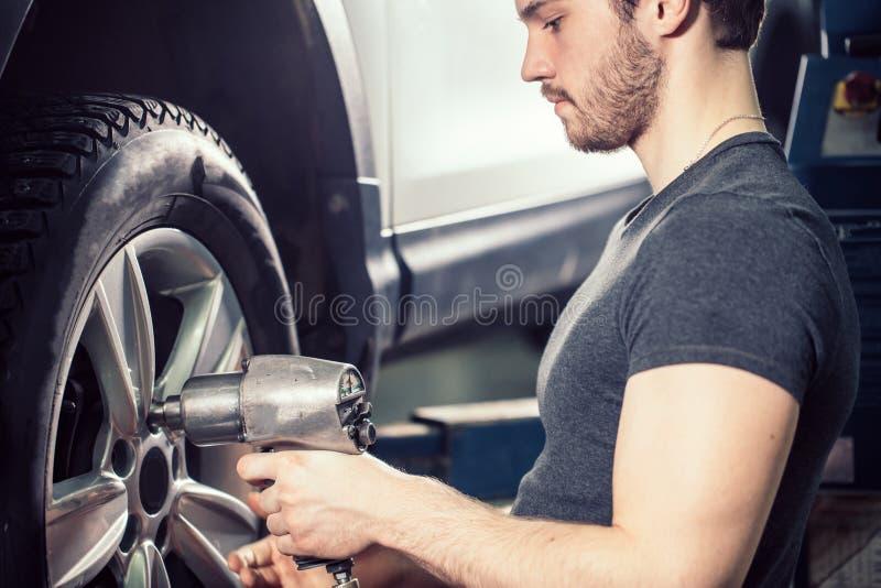 L'automobile cambiante del meccanico spinge dentro il garage della riparazione automatica immagine stock libera da diritti