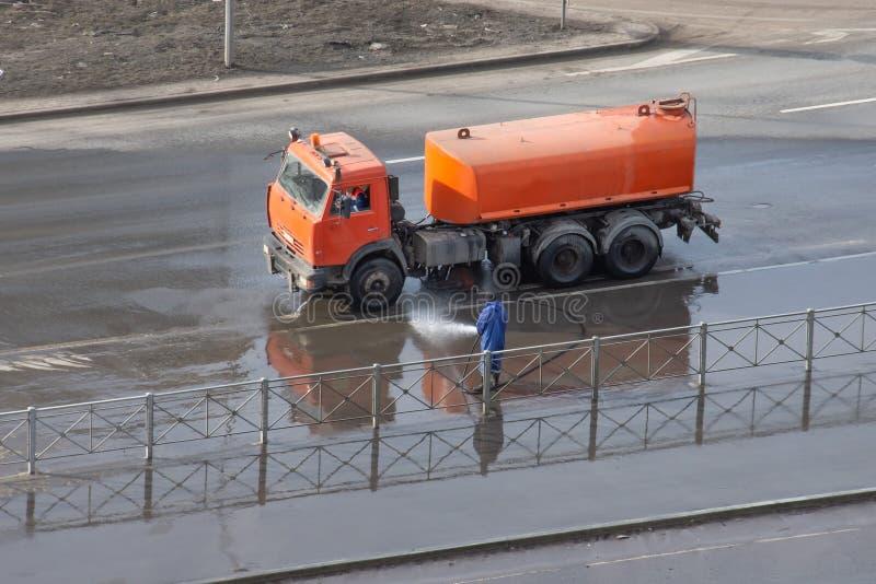L'automobile con un serbatoio di acqua sulla strada principale, un lavoratore lava un asfalto del divisorio mediano da un tubo fl immagini stock