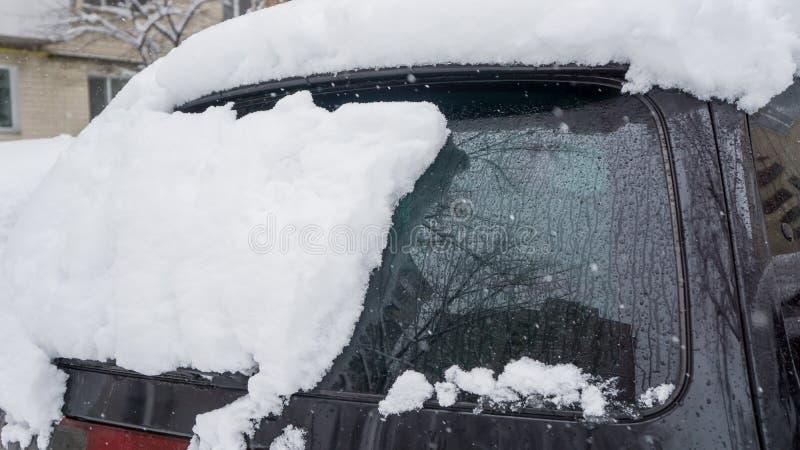L'automobile, coperta di strato spesso di neve Conseguenza negativa delle precipitazioni nevose pesanti automobili parcheggiate c immagini stock libere da diritti
