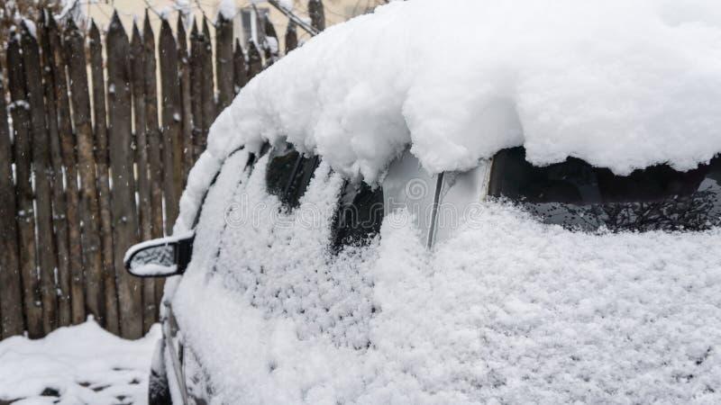 L'automobile, coperta di strato spesso di neve Conseguenza negativa delle precipitazioni nevose pesanti Automobili parcheggiate fotografie stock libere da diritti