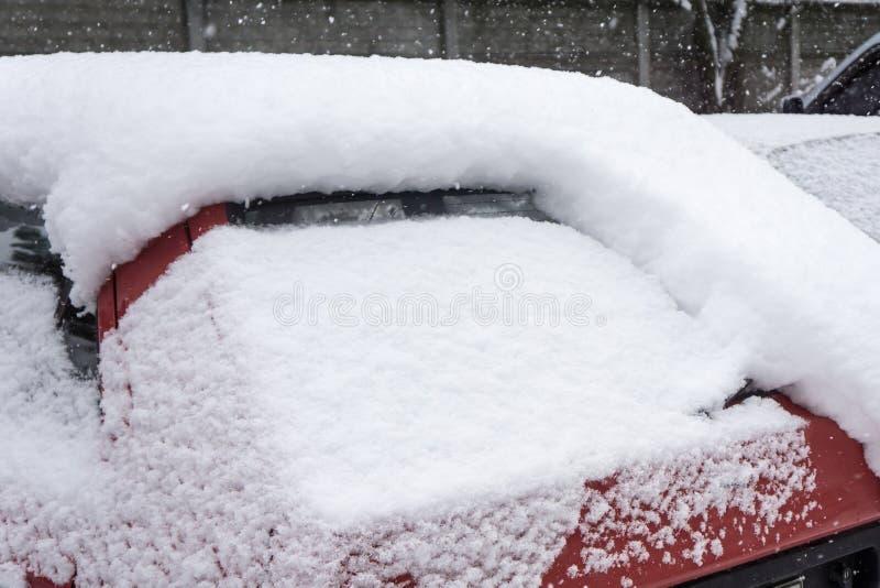 L'automobile, coperta di strato spesso di neve Conseguenza negativa delle precipitazioni nevose pesanti Automobili parcheggiate fotografia stock