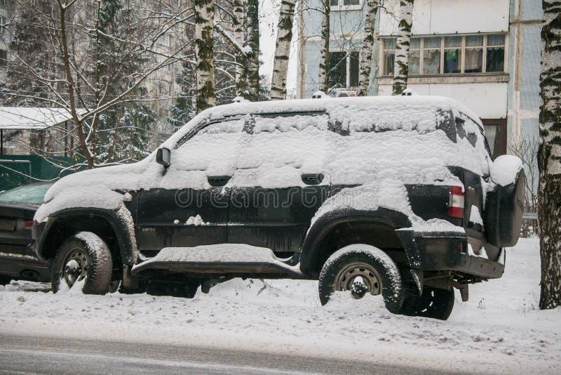 L'automobile, coperta di strato spesso di neve, nell'iarda della casa residenziale in città provilcial fotografie stock libere da diritti