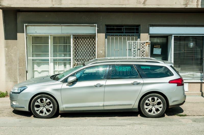 L'automobile d'argento del caravan dell'attrazione di Citroen C5 ha parcheggiato sulla via fotografia stock libera da diritti